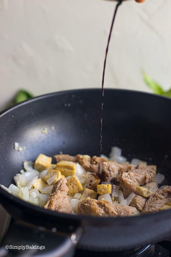 adding soy soauce to the sauteed tofu and seitan for vegan kare kare recipe