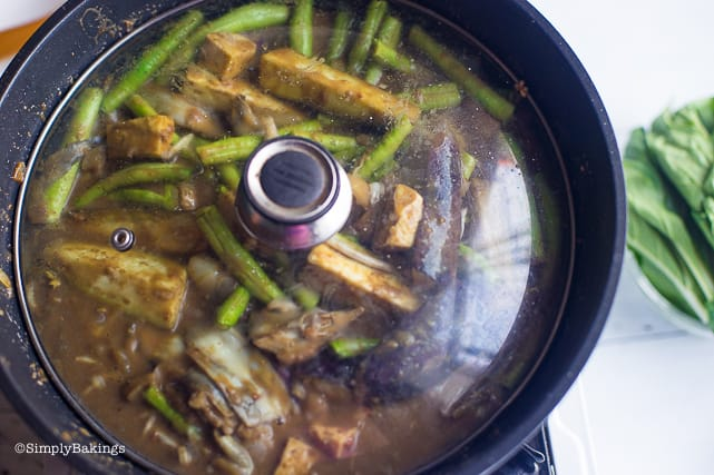 covering the pan to cook the vegetables for the vegan kare kare