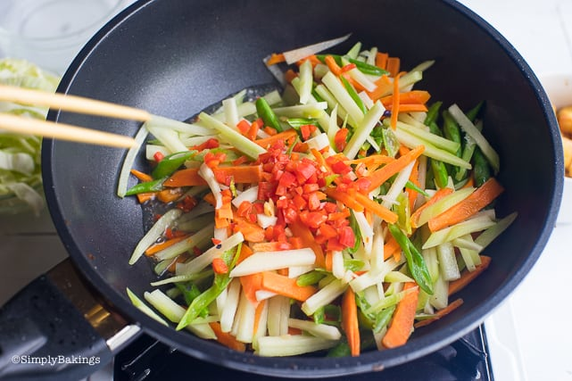 cooking the vegetables in the pan for the pancit bihon recipe