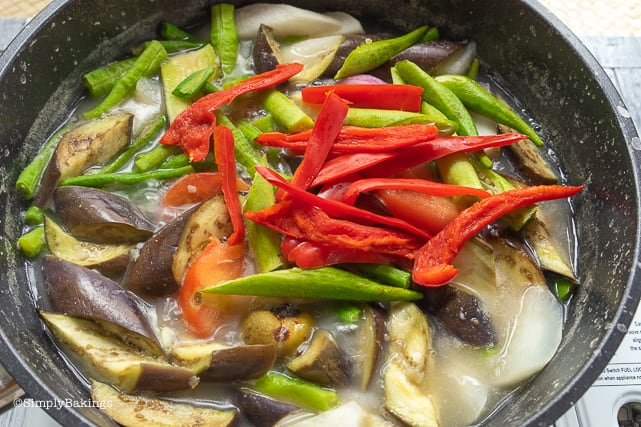 adding the batuan, ginger, okra and red bell peppers to the cooked vegetables for vegetarian sinigang