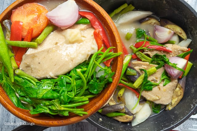 vegetarian sinigang with vegetarian salmon in a wooden bowl