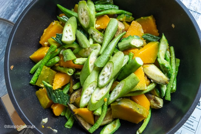 adding the ampalaya, okra and string beans to the ingredients of Pinakbet recipe