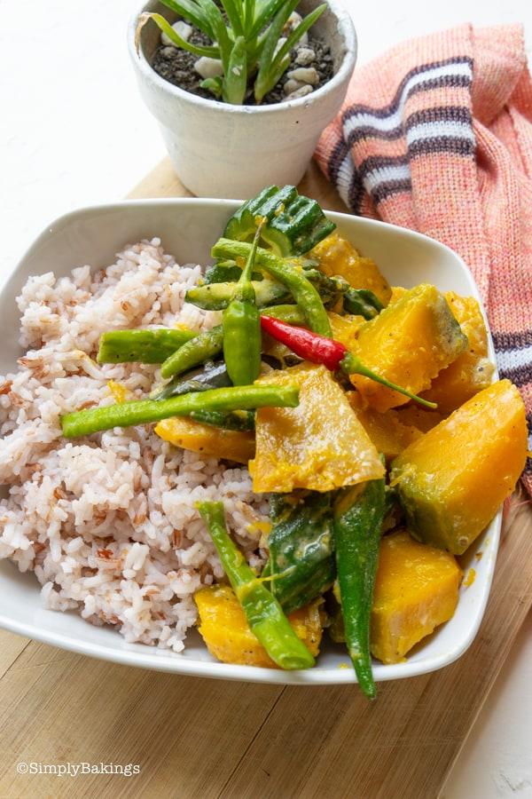 delicious and easy to cook Pinakbet over steamed red rice in a white plate