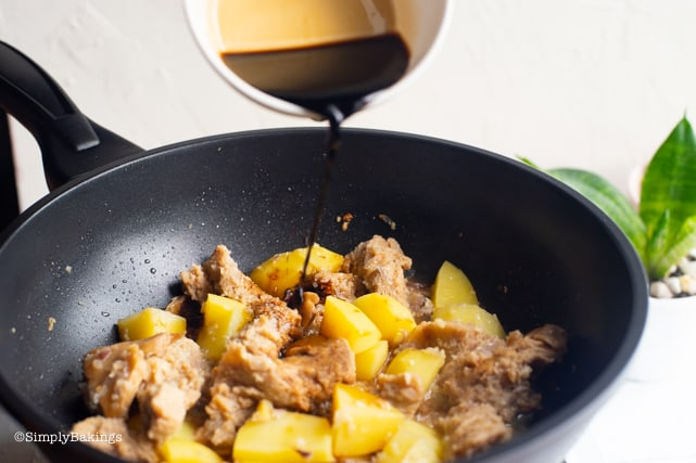 adding soy sauce to the adobo