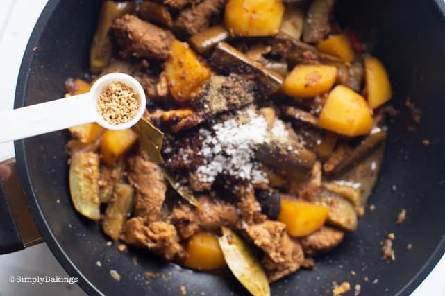 seasoning the vegetarian Filipino Chicken Adobo with mushroom powder for added taste