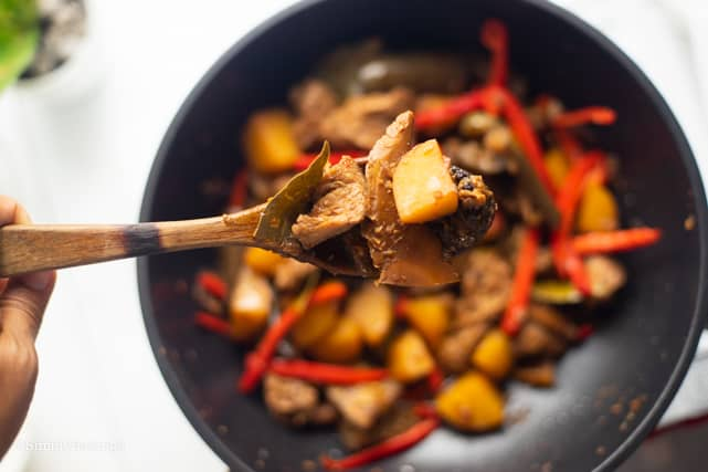 cooked vegetarian Filipino Chicken Adobo in a pan and wooden ladle