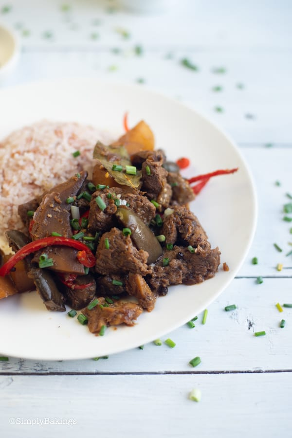 vegetarian Filipino Chicken Adobo with brown rice on a white plate garnished with green onion leaves