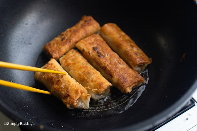 turning the golden brown vegetable lumpiang shanghai with a chopstick