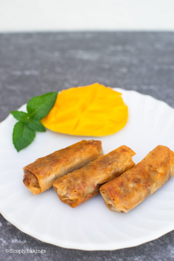 freshly fried vegetable lumpiang shanghai with a slice of mango on a white plate