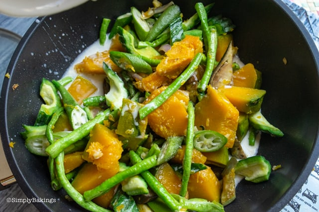 adding in coconut milk to the vegetables of Pinakbet recipe
