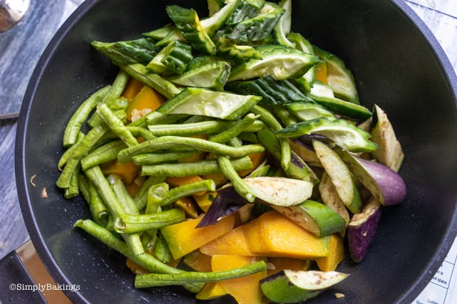 adding ampalaya, string beans and eggplant to the sauteed kalabasa for Pinakbet recipe