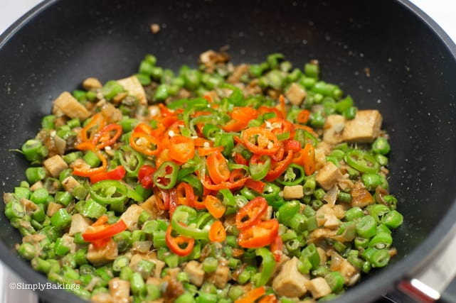 adding in the chili peppers for the vegetarian Bicol express recipe
