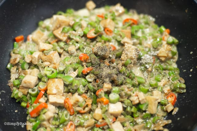 seasoning the vegetarian Bicol Express with salt and pepper to taste