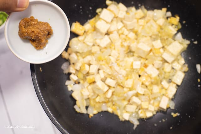 adding bean paste to the sauteed onion, garlic and tofu