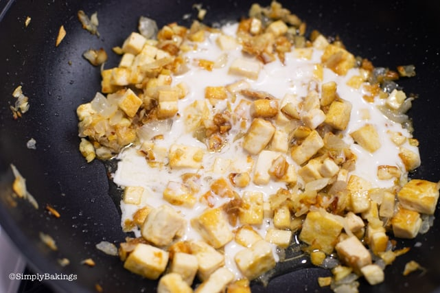 adding coconut milk and soy sauce to the tofu and spices for vegetarian Bicol express recipe