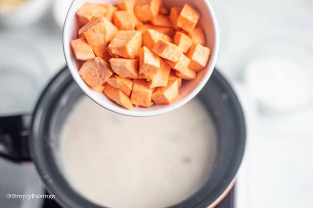 adding the orange sweet potatoes to the binignit