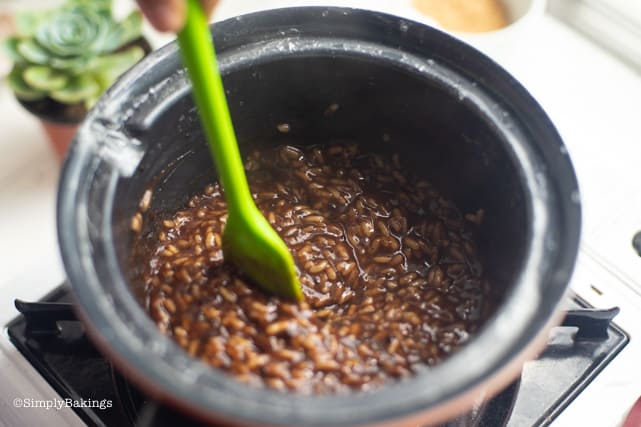 mixing the vegan filipino champorado with a green ladle