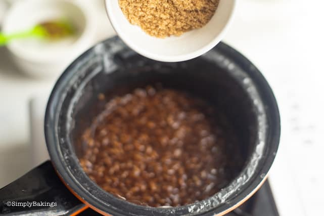 adding the brown sugar to the boiling champorado