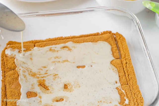 pouring the cream and milk mixture on top of the honey graham crackers