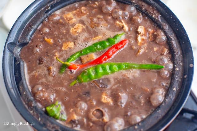 adding chilis to the vegan dinuguan