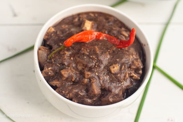 vegan dinuguan in a bowl with red chili on top