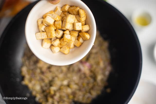 adding the fried tofu to the ginisang monggo in the pan
