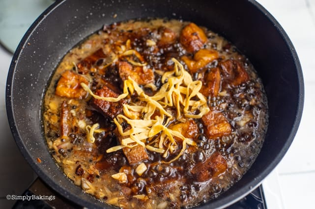 adding banana blossoms and salted black beans to the vegan humba