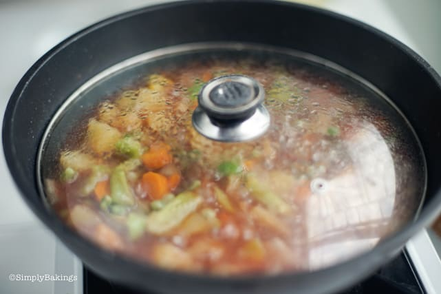simmering the vegan chicken afritada in a covered pan