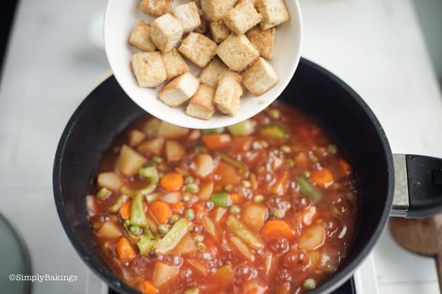 adding the fried tofu cubes to the rest of the vegan chicken afritada ingredients