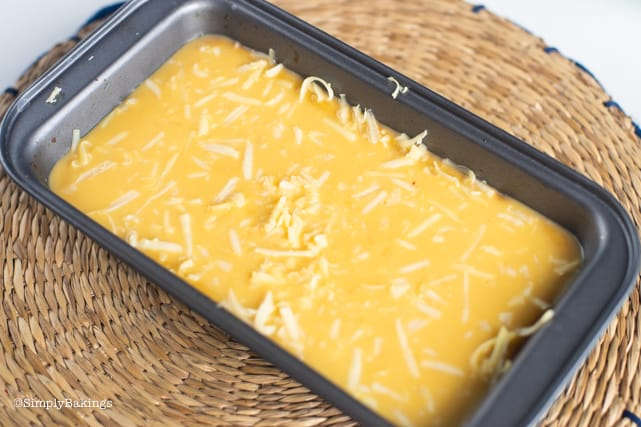 adding grated cheese on top of the cassava cake with custard topping
