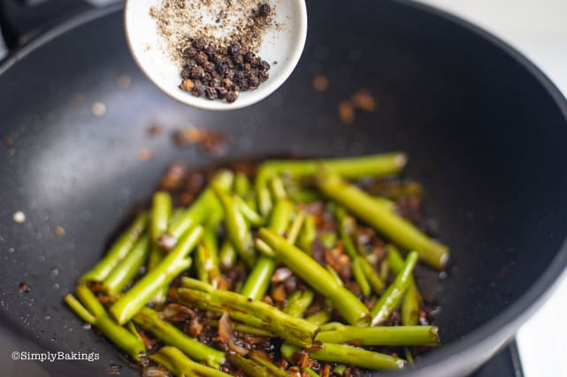 Adding peppercorns for Adobong kangkong recipe
