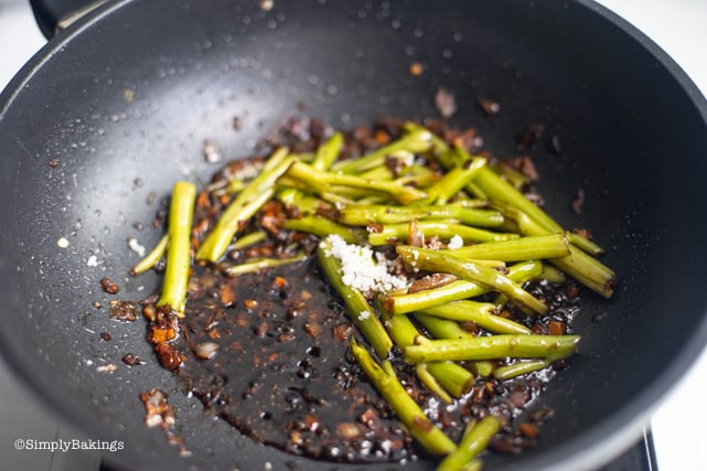 adding salt to the stir-fried kangkong stalks