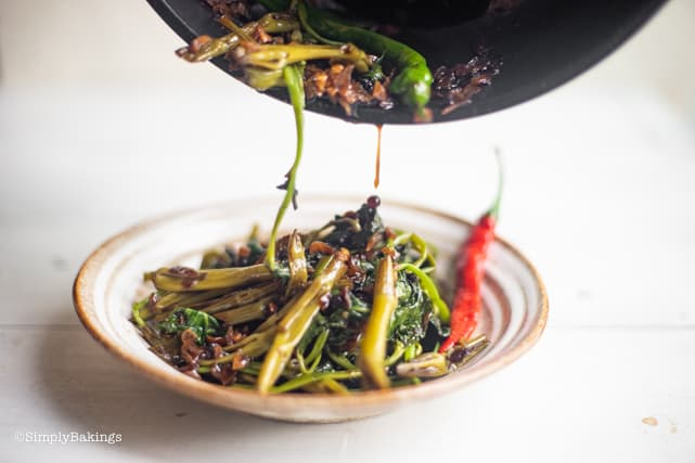 transferring adobong kangkong from the pan to the plate
