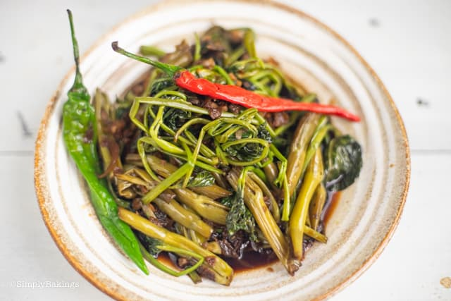 Adobong Kangkong on a plate with green and red chilis