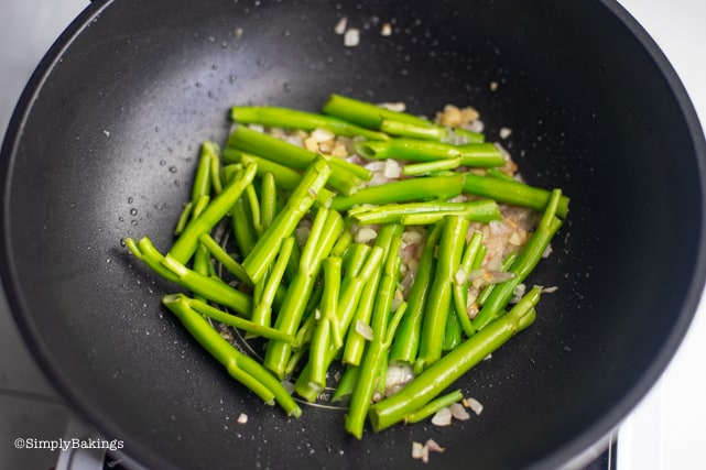 stir frying the stalks of the kangkong for Adobong kangkong recipe