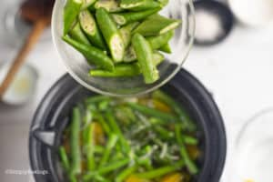 adding the sliced okra to the pot of boiling water