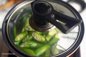 cooking Laswa soup ingredients in a covered pot
