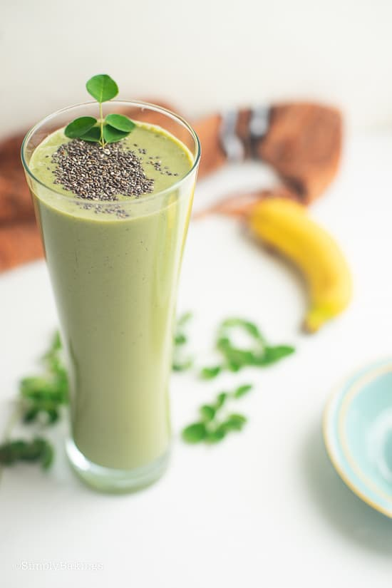 tropical green smoothie garnished with chia seeds and malunggay leaves
