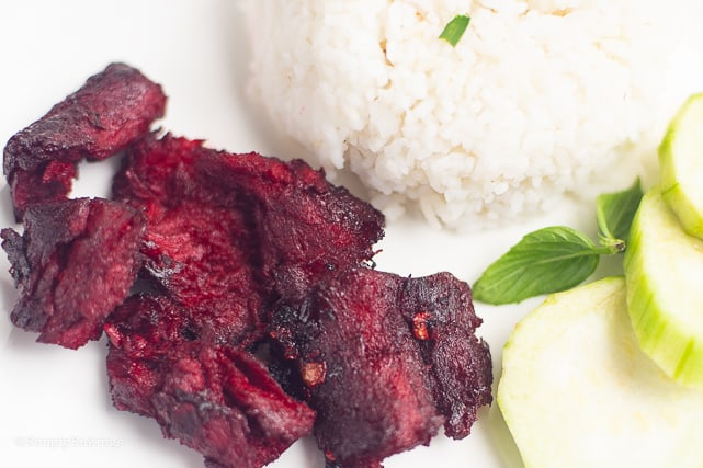Vegan Tocino on a white plate with rice and cucumber slices