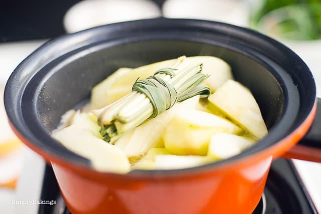 adding lemongrass and papaya slices to the Binakol soup