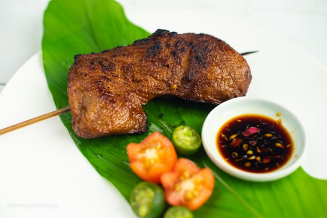 freshly grilled vegan chicken inasal on a wooden skewer placed on banana leaf
