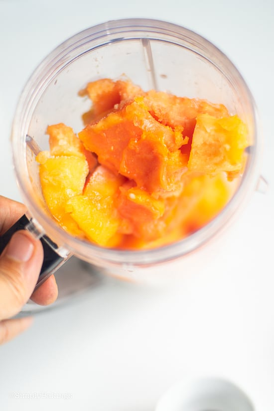 Vegan papaya banana smoothie ingredients in a blender