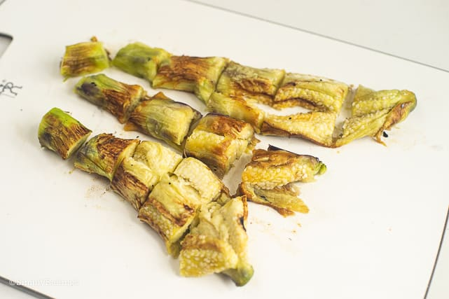 sliced grilled eggplant on a white chopping board