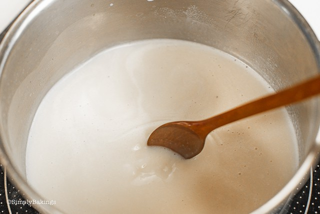 boiling soy milk in a pan and stirring it using a wooden ladle