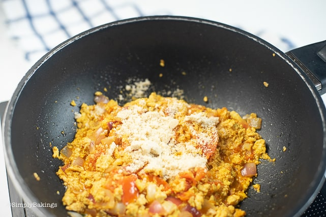 adding garlic powder to the tofu scramble