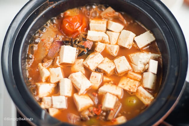 cansi soup boiling with tofu cubes