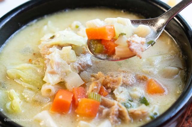 vegan macaroni soup in a black bowl with spoon