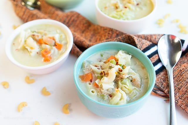 three bowls of vegan macaroni soup with spoon