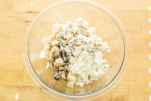 tofu cubes, soy sauce, onions and sesame seeds in a bowl
