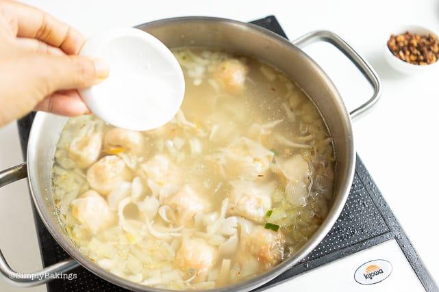 adding salt to the vegetarian pancit molo soup
